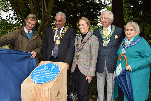 A group of people gathered to watch un unveiling of the Wytham Woods blue plaque